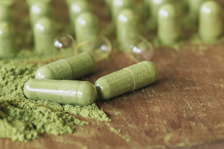 Herbal medicine in capsules with green powder herbs on wooden table