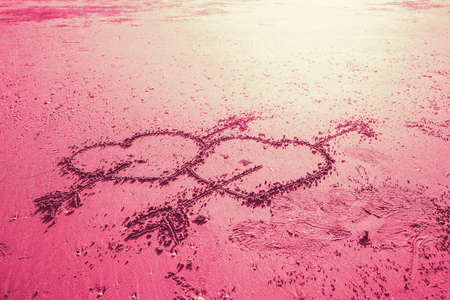 two love heart sign with cupid arrow hand draw on the beach pink sweet color tone