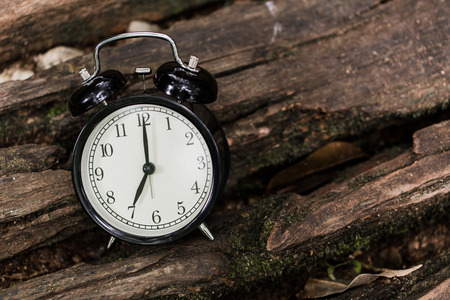 Vintage style old clock on wood background time at 7 oclock morning Stock Photo