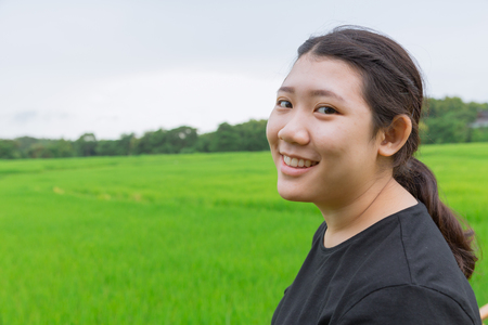 cute young innocent asian teen smile with green rice field in asian countryside nature background Stock Photo