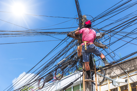 no safety worker technician installing Internet cables on the electricity poles in asian country