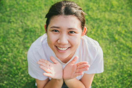 cute young innocent asian teen smile with green grass background 스톡 콘텐츠