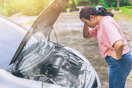 Aziatische vrouwen maken zich zorgen en benadrukken een probleem met oververhitting van de motor van een auto Stockfoto