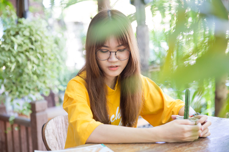 Beautiful cute portait asian teen with glasses sitting in the garden cafe 版權商用圖片