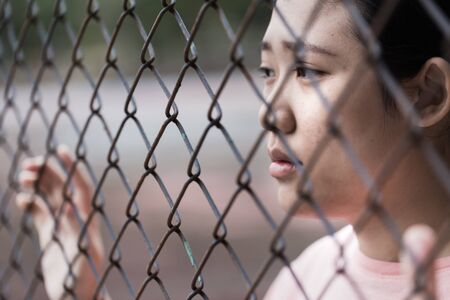 prison asian teen behide cage with sad in jail Stock Photo