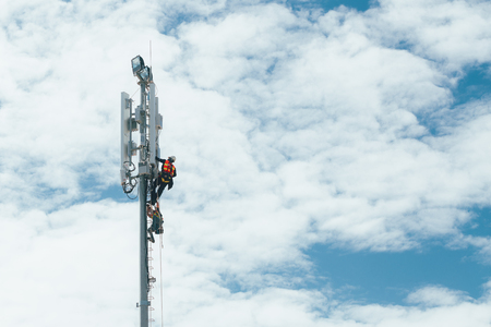 Technician working on communication tower with engineer for digital age development concept