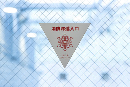Firefighter windows entrance sticker in Japan building with Japanese warning text translation is Fire Fighting Access Do Not Obstruct