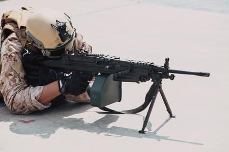 military army soldier lies prone on a firing Machine Gun M249 closeup