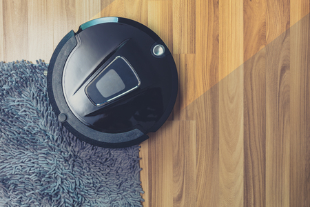 Robot vacuum cleaner cleaning on dusty wooden floor and carpet Reklamní fotografie