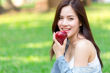 Asian young beautiful girl with red apple on a background of green nature 免版税图像