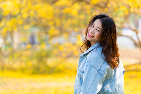 Cute Asian women cute young teen smile happy with yellow flower blur background and space for text Banco de Imagens
