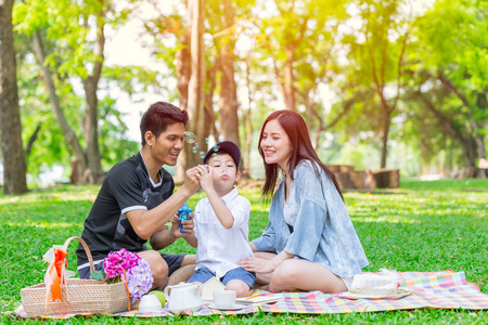 Asian teen family one kid happy holiday picnic moment in the park Stock Photo