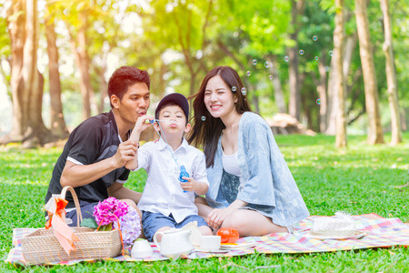 Glücklicher Urlaubspicknickmoment der asiatischen jugendlichen Familie im Park Standard-Bild