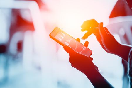 Gente di affari che utilizza smartphone con alla ricerca del grafico aziendale sullo schermo Archivio Fotografico
