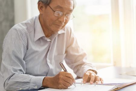 Escritura de la mano de trabajo mayor asiático o contrato de seguro de la firma para el concepto futuro