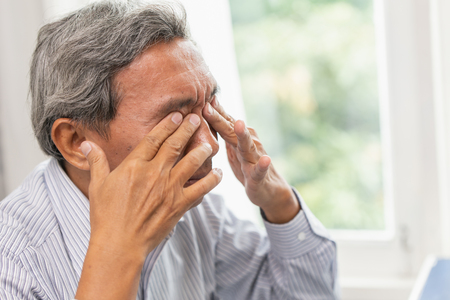 Asian Elderly Self Eye Soothing Massage from irritation problem fatigue and tired after hard work or computer vision syndrome