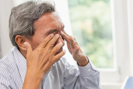 Masaje calmante de ojos asiático para ancianos por irritación, problema de fatiga y cansancio después de un trabajo duro o síndrome de visión por computadora