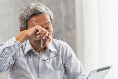 Asian elderly eye irritation problem fatigue and tired from hard work or computer vision syndrome
