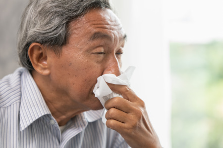 Asian Old man elder get sick wipe the nose snot from flu and runny nose when season change. 免版税图像