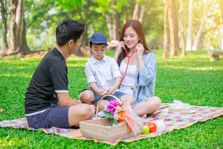Asian teen family one kid happy holiday picnic moment play role as doctor in the park.