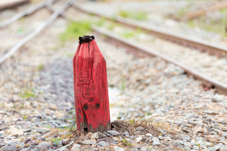 Old Wooden red pillar for warning in the split railroad tracks decision and milestone concept