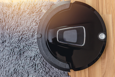 Automate Robot vacuum cleaner on laminate wood floor with carpet cleaning machine.