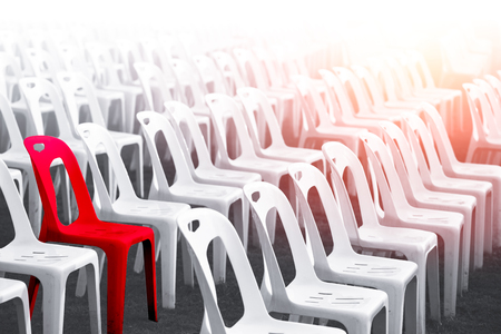 difference red color chair around with many white chairs for unique outstanding person concept
