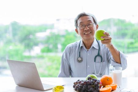 Médico con frutas recomienda comer una dieta saludable, fibra, manzana verde baja en grasa y leche. Enfoque selectivo en Apple. Foto de archivo