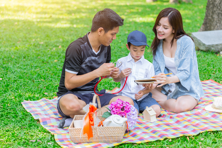 Asian teen family teaching son homework while picnic at outdoor park