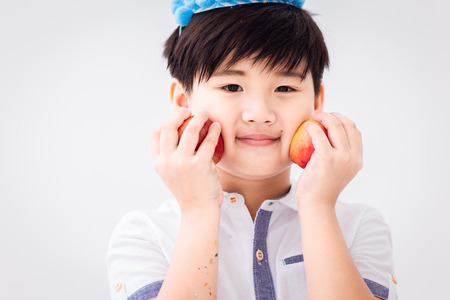 Healthy cute boy with fruit apple on white with copy space for text. Stock Photo