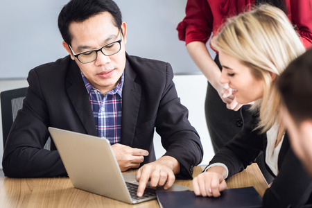 business people talking together look at computer laptop in meeting room mix race asian and caucasian.