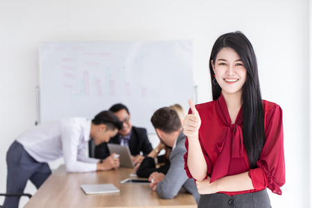 Asian young business girl thumbs up with office teamwork background.