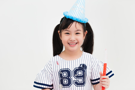 Cute Asian girl child in party hat with sweet candy isolated on white studio background. Stock Photo