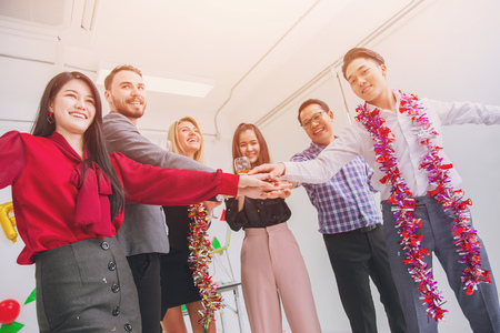 business people join hand together in office party colorful. Stock Photo