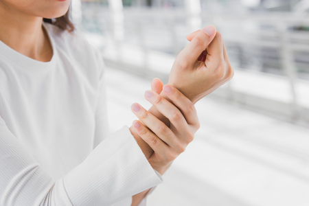 closeup business women holding rub her wrist pain from using computer. Office syndrome joint pain by occupational disease.