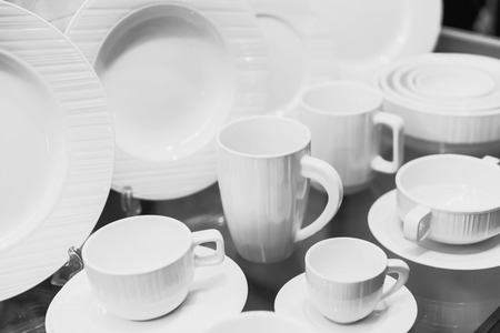 Set of clean white ceramic tableware dish and cups.