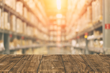 Warehouse inventory in blur for background with empty wooden foreground space.