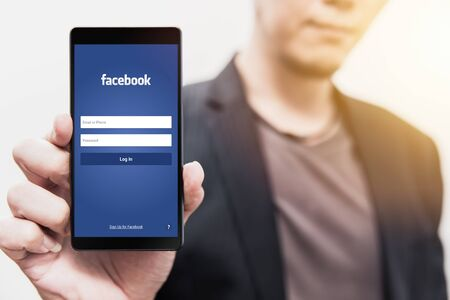 businessman show Facebook login page on his smartphone for using phone social app for business. 3 August 2018, Bangkok, Thailand.