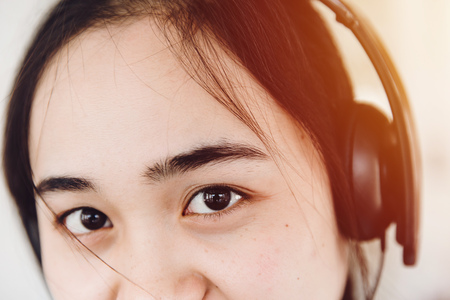 asian eye looking with dark black eyebrows black hair cute teen young wearing headphone.