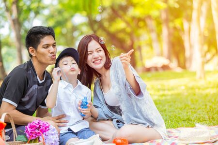 Asiatische Familie, die es genießt, zusammen Bubble im Green Park zu spielen Natürlicher Hintergrund im Freien