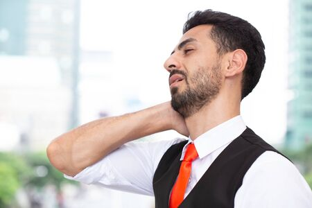 Latin Businessman neck pain, fatigue from hard work office syndrome