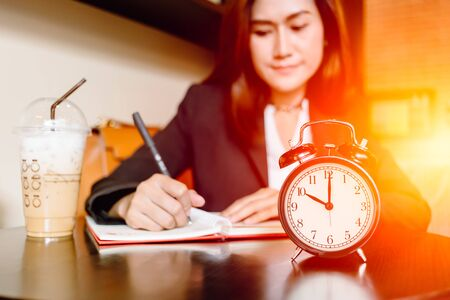 Asian Business girl working hours in cafe with time clock and coffee happy enjoy mood