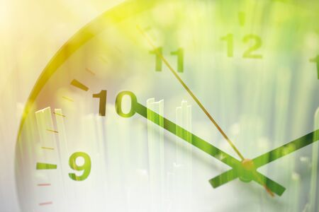Times clock face overlay with green grass nature background. time to saving environment ecology concept Stock Photo