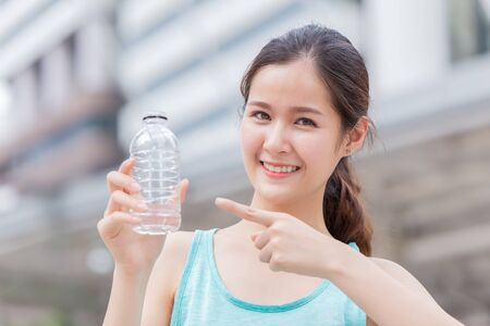 Girl teen with drink water bottle for suggest to drinking water and recycle PET plastic garbage