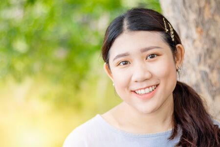 Innocent beautiful cute girl teeth smiling  portly shape healthy Asian race outdoor green nature. Archivio Fotografico - 132012863