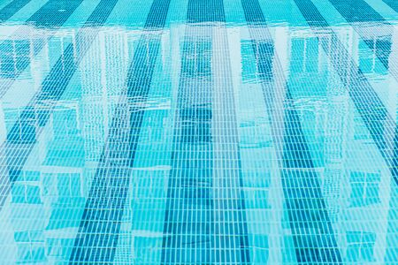 swimming pool clean new blue clear water with mosaic line pattern for background Banque d'images