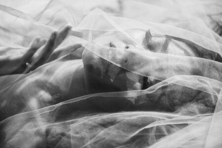 Primo piano Sexy viso di donna erotica sotto vedere attraverso il tessuto con fotografia d'arte monotona. Archivio Fotografico