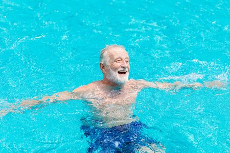 Healthy elder happy enjoy and laugh in the swimming pool in the summer season.