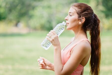 Thirsty beautiful sport women model handle drink clean drinking water outdoor after exercise.
