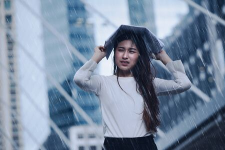 Girl in the heavy rain storm cover head with newspaper for economic obstacle passing concept.